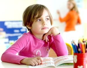 Фото - Дівчинка сидить на уроці за партою
